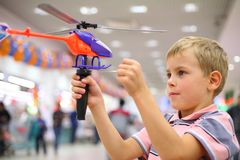 Boy in shop with toy helicopter Stock Photos