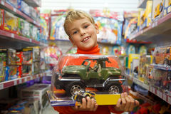 The boy in shop with the toy machine in hands Stock Photography