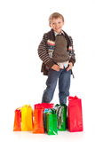 Boy with shopping bags. Smiling boy stood with colorful shopping bags, isolated on white background stock image