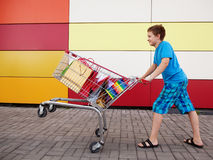 Young buyer. Boy with shopping trolley full of purchases in the street Stock Photography