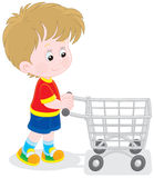 Boy with a shopping trolley. Little buyer going with a supermarket trolley to do shopping Stock Photography