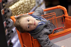 Boy in shopping trolley Stock Images