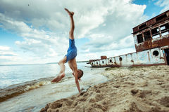 Boy shorts is happy jumps and flips on the beach. In summer Royalty Free Stock Photos