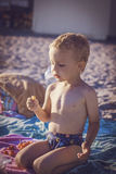 Boy in shorts sitting on the beach and eating cherries Royalty Free Stock Photos