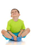 Boy in shorts and a t-shirt sitting on the floor Stock Photography