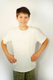 Boy in shorts and white shirt stands and smiles Stock Photography