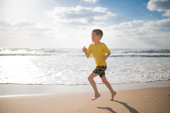 Boy in shorts and a yellow T-shirt. Runs along the sea Stock Photos