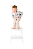Boy shot in the studio on a white background bended over. Boy in shirt shot in the studio on a white background Royalty Free Stock Photo