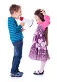 Boy shouting at girl with megaphone. Little boy shouting at girl with megaphone Stock Photos