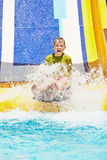 Boy shouts while slides down water-slide. At summer stock image
