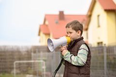 Boy shouts something into the megaphone Royalty Free Stock Photo