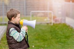Boy shouts something into the megaphone Stock Image