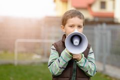 Boy shouts something into the megaphone Stock Photos
