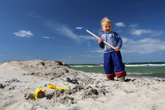 Boy with a shovel at the beach Stock Photos
