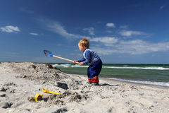 Boy with a shovel at the beach Royalty Free Stock Photo