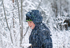 Boy with shovel playing in snow forest Royalty Free Stock Images