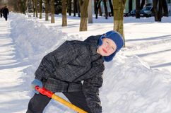 Boy with a shovel after a snow fall. Stock Photos