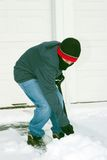 Boy Shoveling Snow. Dressed in jeans, boots, hat, gloves and a scarf Royalty Free Stock Images