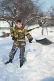 Boy shoveling snow from walkway Royalty Free Stock Images