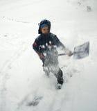 Boy shovels snow stock images