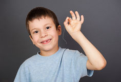 Boy show lost tooth on a thread Royalty Free Stock Images