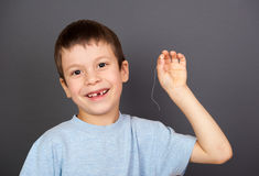 Boy show lost tooth on a thread Royalty Free Stock Photography