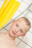 Boy in shower holding paddles from boat Stock Photography