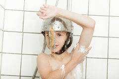 Boy showering in knights helmet Royalty Free Stock Photos