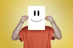 Boy showing a blank paper with a happy emoticon. In front of his face Stock Image
