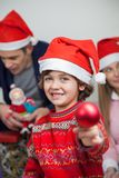 Boy Showing Christmas Decoration At Home Royalty Free Stock Image