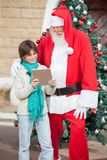 Boy Showing Digital Tablet To Santa Claus Stock Photos