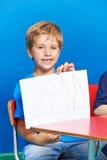 Boy showing drawing in kindergarten Stock Photo