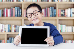 Boy showing empty tablet screen in library Stock Photography