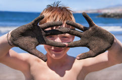 Boy is showing hands in the sand. Royalty Free Stock Images