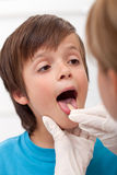 Boy showing her throat to health professional Royalty Free Stock Images