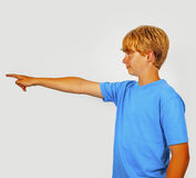 Boy showing with his arm in the foreward direction Stock Image