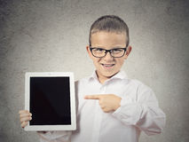 Boy showing his new pad computer. Closeup portrait happy, smiling young boy, child shows tablet with touchscreen display, pointing with finger isolated grey wall Stock Image