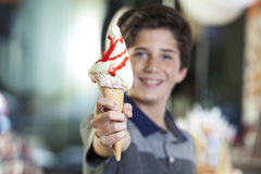 Boy Showing Ice Cream With Strawberry Syrup In Parlor. Portrait of happy preteen boy showing delicious ice cream with strawberry syrup in parlor Stock Images