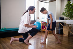 Boy showing knee to female therapist kneeling on hardwood floor. At hospital ward Stock Photo