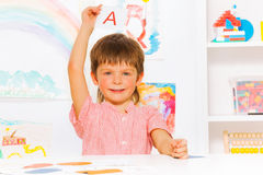 Boy showing letter flashcard in reading class Royalty Free Stock Image
