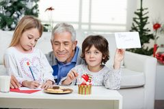 Boy Showing Letter While Grandfather Assisting Stock Images
