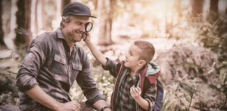 Boy showing magnifying glass to father while hiking in forest Stock Photos