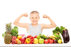 Boy showing muscles behind pile of vegetables Stock Photography