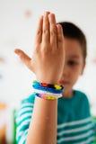 Boy showing rubber bracelets Royalty Free Stock Image