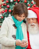 Boy Showing Smartphone To Santa Claus Stock Photography