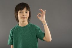 Boy showing something on the palm of his hand on a gray backgrou Royalty Free Stock Photo