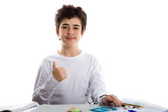 Boy showing success gesture on homework blank book Royalty Free Stock Photos