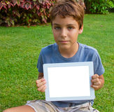 Boy showing tablet PC. Boy  showing tablet  PC on green grass lawn with copy space Stock Photo