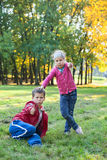 Boy showing thumb up and girl thump down in autumn park Royalty Free Stock Images