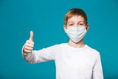Boy showing thumb up in protection mask Stock Photography
